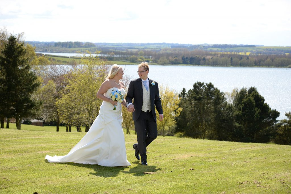 A bride and groom with Rutland Water in the background